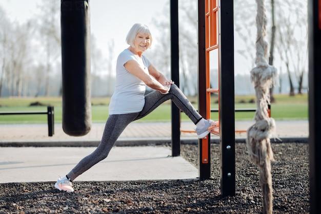 Se sentir bien. femme blonde exubérante portant des vêtements de sport et exerçant en plein air