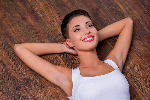 Se sentir calme et détendu. vue de dessus de la belle jeune femme aux cheveux courts tenant les mains derrière la tête et souriant en position couchée sur le plancher de bois franc