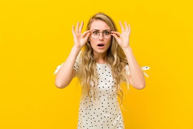 Se sentir choqué, étonné et surpris, tenant des lunettes avec un regard étonné et incrédule