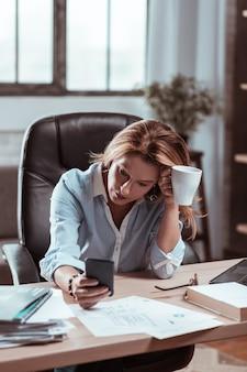 Se sentir concerné. femme d'affaires aux cheveux blonds buvant du thé et se sentant préoccupée par le nouveau projet