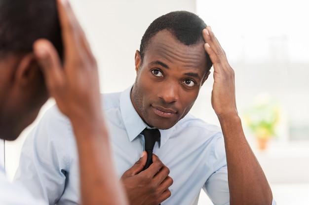 Se sentir confiant dans son look. jeune homme africain regardant le miroir et ajustant sa cravate