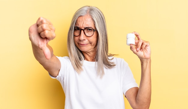 Se sentir contrarié, en colère, agacé, déçu ou mécontent, montrant les pouces vers le bas avec un regard sérieux et tenant une bouteille de pilules