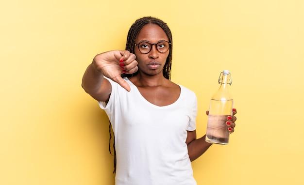 Se sentir contrarié, en colère, ennuyé, déçu ou mécontent, montrant les pouces vers le bas avec un regard sérieux. concept de bouteille d'eau