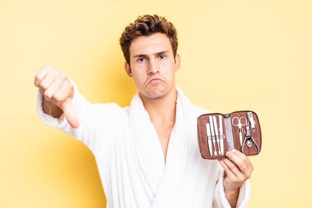Se sentir contrarié, en colère, ennuyé, déçu ou mécontent, montrant les pouces vers le bas avec un regard sérieux. concept de cas d'outils d'ongles
