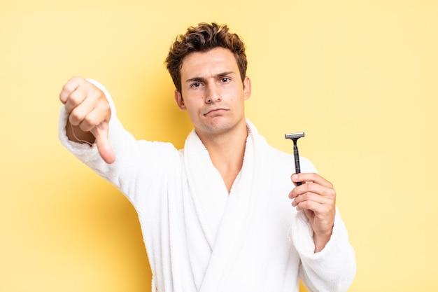 Se sentir contrarié, en colère, ennuyé, déçu ou mécontent, montrant les pouces vers le bas avec un regard sérieux. concept de rasage