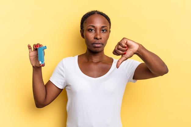 Se sentir contrarié, en colère, ennuyé, déçu ou mécontent, montrant les pouces vers le bas avec un regard sérieux. notion d'asthme