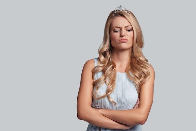 Se sentir déçu. jeune femme fière en couronne gardant les bras croisés et faisant une grimace en se tenant debout sur fond gris