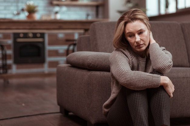 Se sentir déprimé. femme portant un pantalon carré marron se sentant déprimé après des problèmes de travail