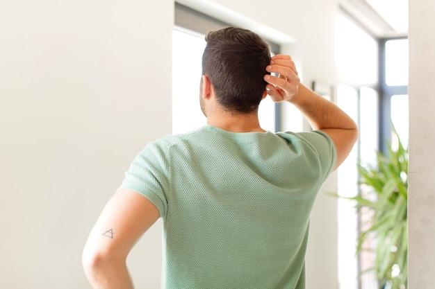 Se sentir désemparé et confus, penser à une solution, avec la main sur la hanche et l'autre sur la tête, vue arrière