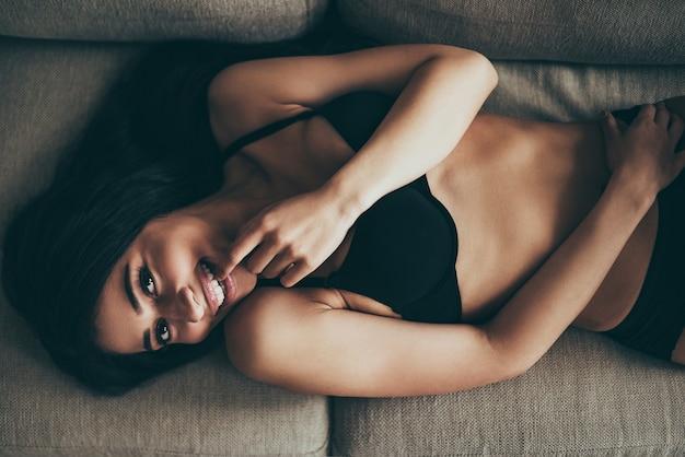 Se sentir enjoué. vue de dessus d'une jeune femme métisse enjouée en lingerie noire regardant la caméra et touchant les lèvres avec le doigt en position couchée sur le canapé