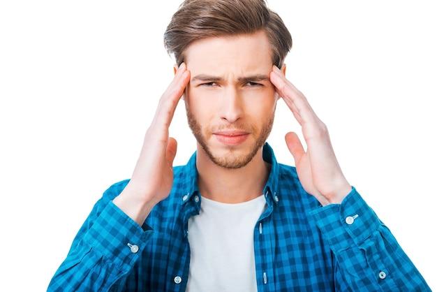 Se sentir épuisé. jeune homme frustré touchant sa tête en se tenant debout sur fond blanc