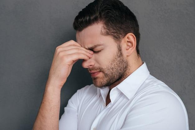 Se sentir fatigué et déprimé. jeune homme frustré touchant son visage avec la main