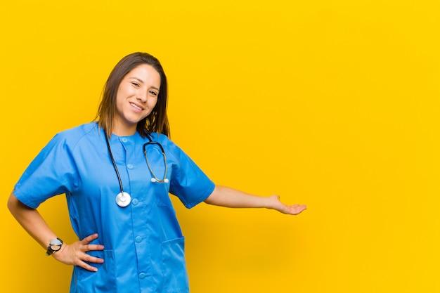 Se sentir heureux et joyeux, souriant et vous accueillir, vous invitant à un geste amical isolé contre le mur jaune