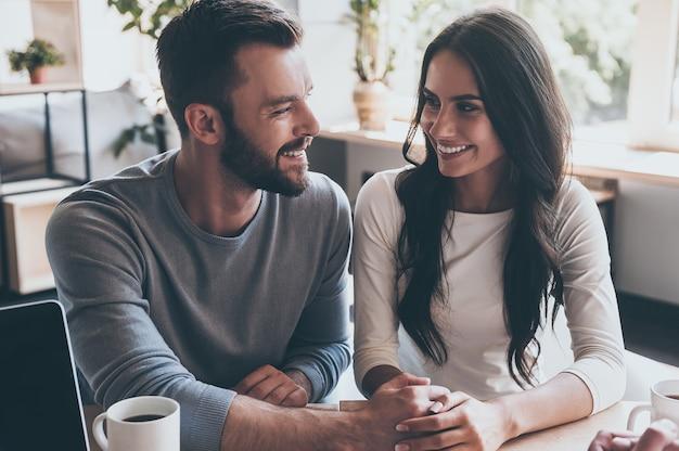 Se sentir heureux maintenant. heureux jeune couple d'amoureux se tenant la main et se regardant tout en étant assis au bureau avec un homme assis devant eux