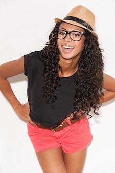 Se sentir heureux avec son style. belle jeune femme africaine à lunettes et vêtements funky tenant les mains sur la hanche et souriant à la caméra tout en posant sur fond blanc