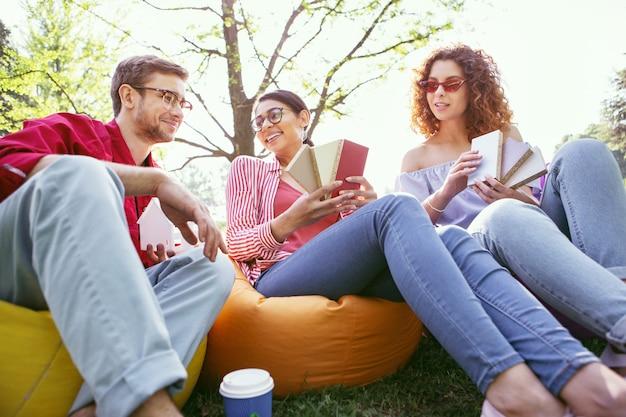 Se sentir inspiré. joyeuse femme brune assise en plein air avec ses collègues et discutant de leur démarrage