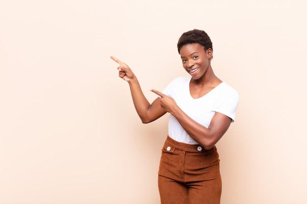 Se sentir joyeux et surpris, souriant avec une expression choquée et pointant vers le côté