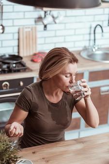 Se sentir mal. femme malade se sentant extrêmement malade et mauvaise eau potable après avoir pris la pilule