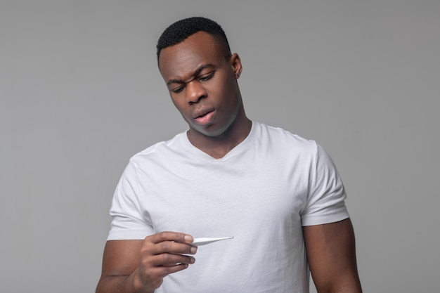 Se sentir mal. jeune adulte bouleversé afro-américain en tshirt blanc regardant thermomètre en main