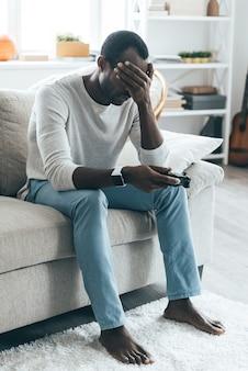 Se sentir mal à propos du jeu. beau jeune homme africain tenant la main sur ses yeux alors qu'il était assis sur le canapé à la maison