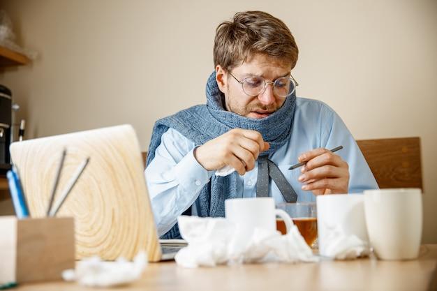 Se sentir malade et fatigué. l'homme avec une tasse de thé chaud travaillant au bureau, homme d'affaires a attrapé la grippe froide et saisonnière. grippe pandémique, prévention des maladies, climatisation dans le bureau causent des maladies