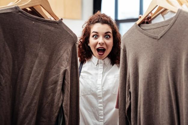 Se sentir occupé. femme brune bouclée se sentant occupée en choisissant une nouvelle chemise dans le centre commercial