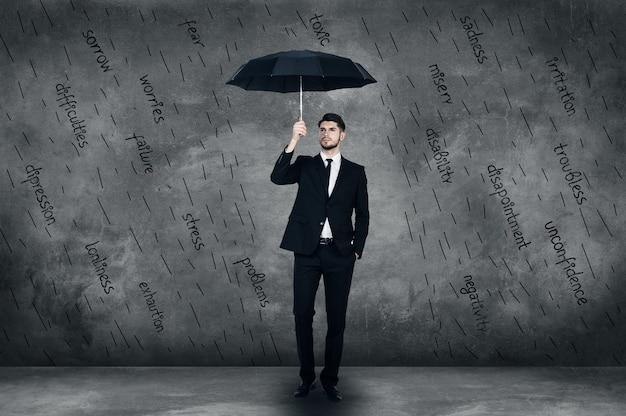 Se sentir protégé. toute la longueur du jeune homme confiant en costume complet tenant des parapluies
