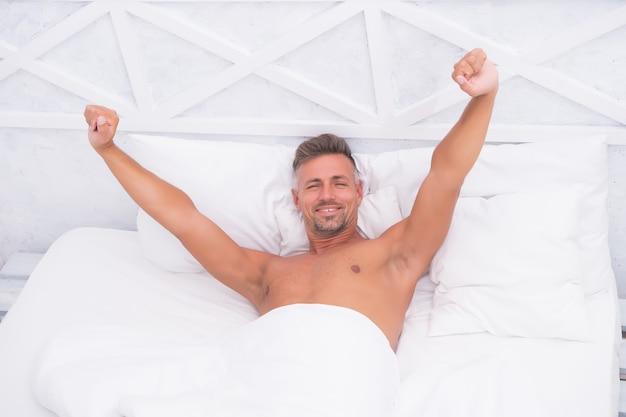 Se sentir rechargé. habitudes saines. l'homme beau mec était allongé dans son lit en train de dormir. conseils pour mieux dormir. homme paisible barbu dormir face à l'oreiller relaxant couverture couverte. détente totale. étirement des mains.
