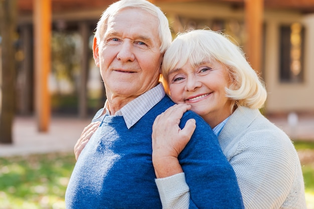 Se sentir en sécurité près de lui. joyeux couple de personnes âgées se liant les uns aux autres et souriant tout en se tenant à l'extérieur et devant leur maison