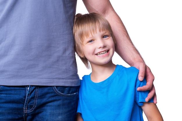 Se sentir en sécurité et protégé. père et fils se tenant près l'un de l'autre pendant que l'enfant regarde la caméra et sourit