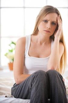 Se sentir si mal. jeune femme frustrée tenant la tête dans la main et exprimant sa négativité alors qu'elle était assise dans son lit dans son appartement