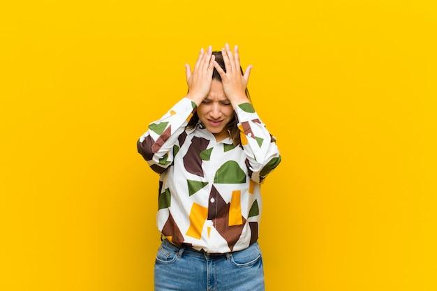 Se sentir stressé et anxieux, déprimé et frustré par un mal de tête, levant les deux mains vers la tête