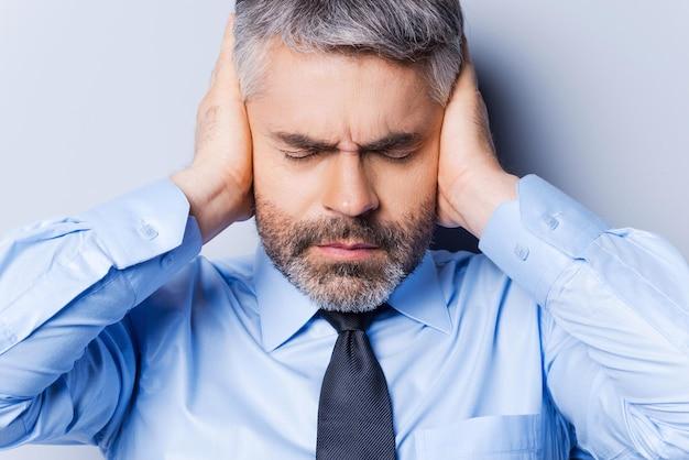 Se sentir stressé et surmené. homme mûr frustré en chemise et cravate couvrant les oreilles avec les mains et gardant les yeux fermés en se tenant debout sur fond gris