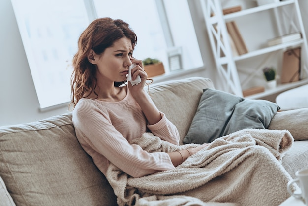 Se sentir tellement triste. jeunes femmes solitaires couvertes d'une couverture qui pleurent alors qu'elles sont assises sur le canapé à la maison