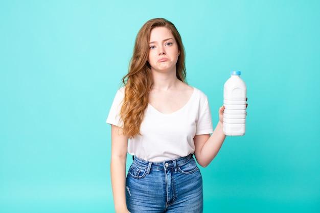 Se sentir triste et pleurnicher avec un regard malheureux et pleurer et tenir une bouteille de lait