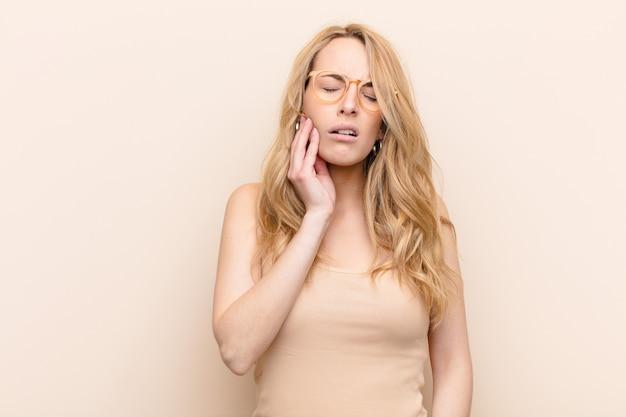 Se tenir la joue et souffrir de maux de dents douloureux, se sentir malade, misérable et malheureux, à la recherche d'un dentiste