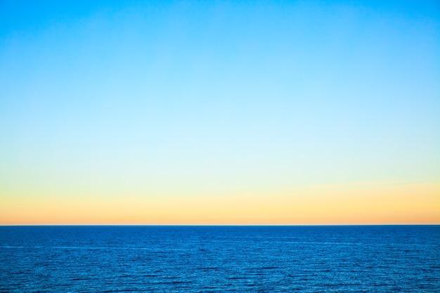 Sea at sundown - beau paysage marin avec un ciel clair. fond minimaliste