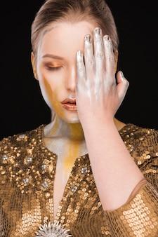 La séance de beauté d'une femme blonde élégante avec de la peinture dorée et argentée couvre son visage à la main