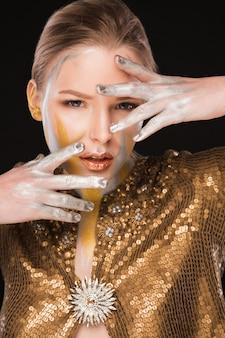 Séance de beauté d'une femme blonde à la mode avec de la peinture dorée et argentée sur le visage et les mains