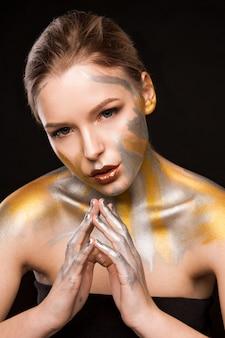 Séance de beauté d'une jolie femme blonde avec de la peinture dorée et argentée sur ses épaules et son visage