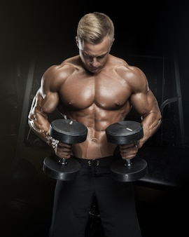 Séance d'entraînement de beau mec athlétique avec des haltères