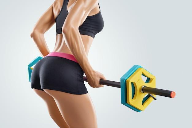 Séance d'entraînement de femme de forme physique avec le barbell au-dessus du backgroun blanc
