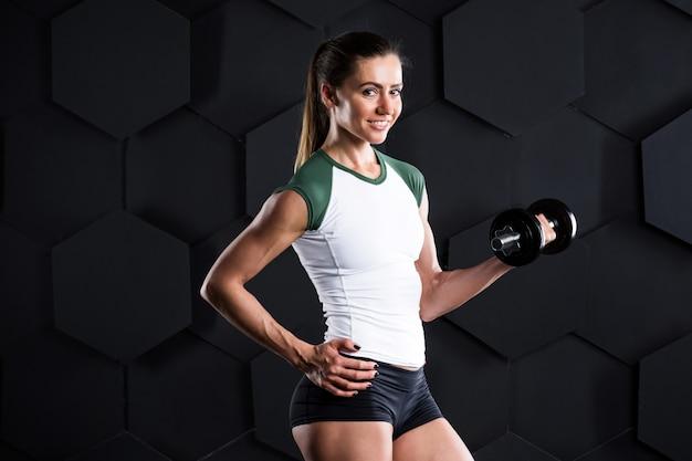 Séance d'entraînement de femme avec des haltères sur dark