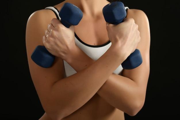 Séance d'entraînement de femme avec des haltères sur le fond noir