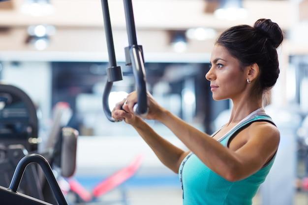 Séance d'entraînement de femme de sport sur la machine d'exercices dans la salle de fitness