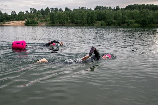Séance d'entraînement de natation en eau libre des athlètes en soirée