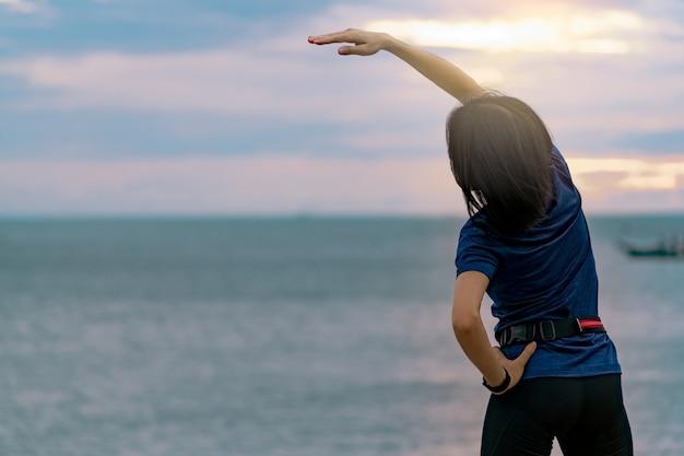 Séance d'entraînement de silhouette femme le matin à la plage de pierre avec un beau ciel de lever de soleil. fit femme coureur étirement du corps avant de courir. exercice cardio pour un mode de vie sain.