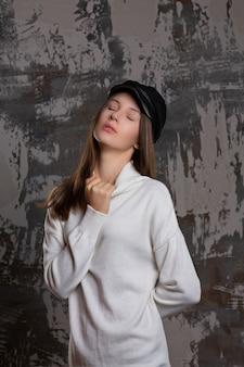 Séance d'essai d'une femme brune sensuelle posant dans une casquette élégante et une robe tricotée