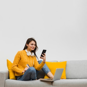 Séance femme, sur, sofa, et, regarder, elle, smartphone