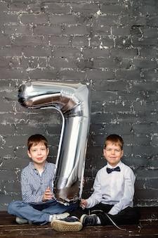 Séance photo avec un ballon de 7 ans. ballon en argent avec numéro 7.